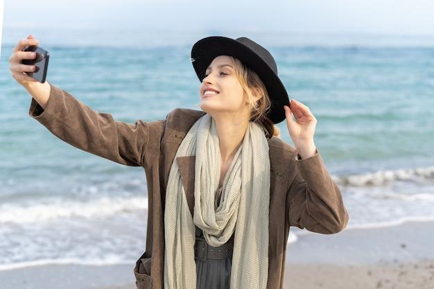 ゴージャスな女の子がビーチで笑顔で自分撮りをしているスタイリッシュな若い女性が携帯電話を持って自分の写真を撮っています