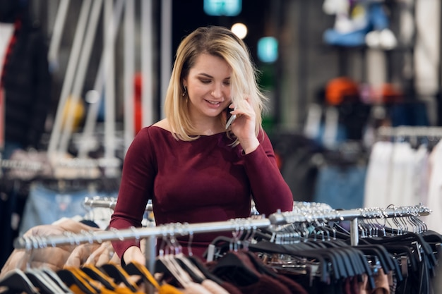 A gorgeous girl receives a phone call in a shopping store