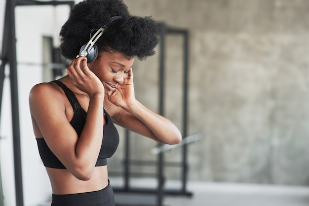 Gorgeous girl testing new headphones. african american woman with curly hair and in sportive clothes have fitness day in the gym
