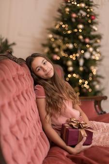 Великолепная девушка с праздничным рождественским подарком в стильном интерьере