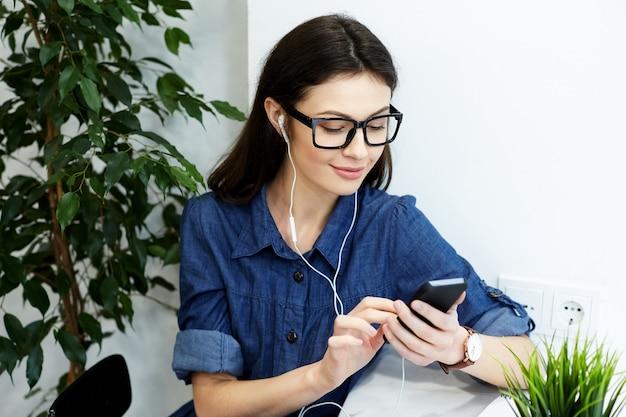 携帯電話とコーヒー、フリーランスのコンセプト、肖像画、音楽を聴いてカフェに座っている青い縞模様のシャツと眼鏡を身に着けている黒髪のゴージャスな女の子。