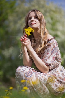 A gorgeous girl with a bouquet of the first summer flowers is sitting on the lawn of the park