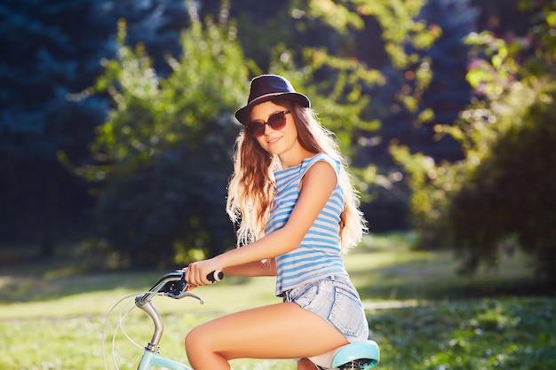 모자, 위쪽 및 공원에서 자전거와 함께 서있는 반바지를 입고, 여행, 초상화, 웃 고 곱슬 머리를 가진 화려한 소녀.