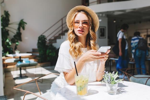 Splendida ragazza con l'acconciatura riccia in attesa amico nel ristorante con interni accoglienti e bere succo ghiacciato