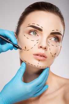 Gorgeous girl with dark eyebrows at studio background, doctor's hands wearing blue gloves drawing perforation lines on face.