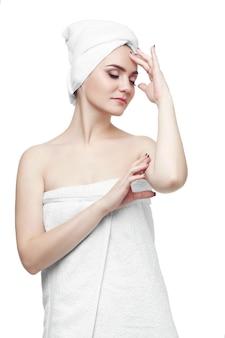 Великолепная девушка с темными волосами и темными бровями, в белом полотенце на голове, держась за руки возле лица. легкий макияж. портрет красивой женщины 20-25 лет с полотенцем на голове