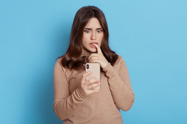 Gorgeous girl with dark hair holding phone in her hand, being surprised by something she saw on screen, has scared expression, biting her finger, wearing casually, isolated