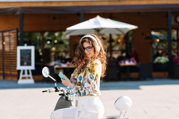 Splendida ragazza con lunghi capelli ricci che indossa una camicia con motivi floreali, seduto su uno scooter e tenendo il telefono cellulare