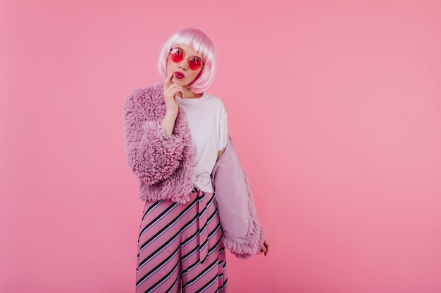 Gorgeous girl with short pink hair posing in trendy sunglasses. indoor photo of interested stylish woman wears fur jacket