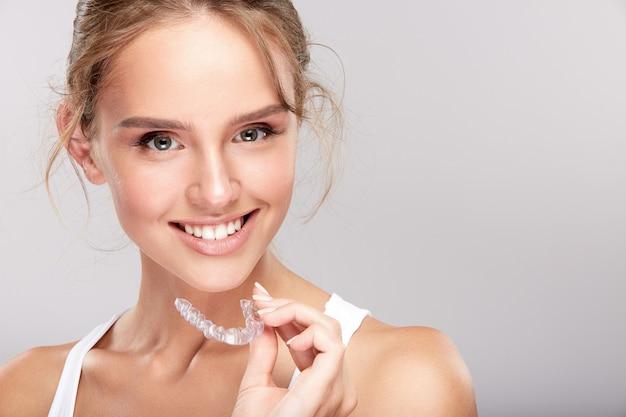 흰색 스튜디오 배경, 치과 개념, 완벽 한 미소에 눈 하얀 이빨을 가진 화려한 소녀, 카메라를보고 닫습니다, 치약을 들고 웃 고.
