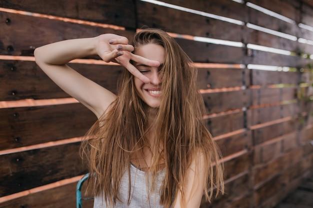 Splendida ragazza con acconciatura dritta scherzare sulla parete di legno. foto all'aperto di giovane donna entusiasta che fa facce buffe.