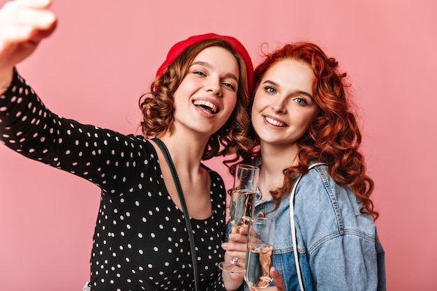 Gorgeous girls drinking champagne with smile. studio shot of adorable young ladies holding wineglasses on pink background.