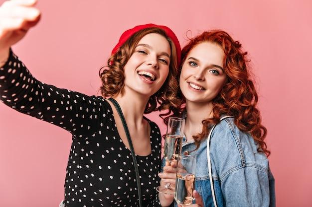 笑顔でシャンパンを飲むゴージャスな女の子。ピンクの背景にワイングラスを保持している愛らしい若い女性のスタジオショット。