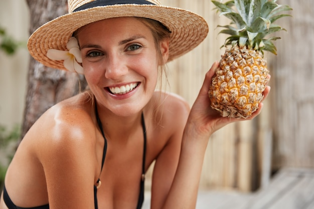 Gorgeous happy female in bikini and summer hat relaxes on spa in tropical hotel, holds pineapple, prepares for party with friends. people, healthy eatting, fruit diet and recreation concept.