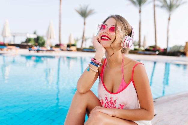 Великолепная счастливая девушка думает о чем-то приятном в ожидании друзей рядом с голубой водой на экзотическом курорте