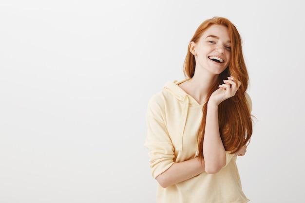 Великолепная счастливая рыжая девушка улыбается и беззаботно смеется