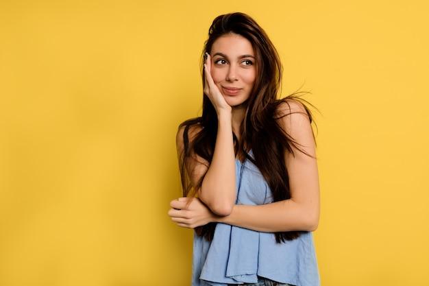 Splendida donna felice in camicia blu che copre il viso con la mano e guarda sognante nella cornice sul muro giallo.