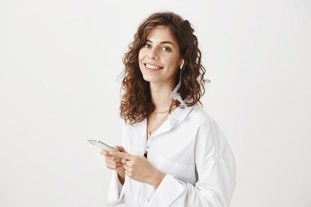 Великолепная счастливая женщина с помощью мобильного телефона, прослушивания музыки в беспроводных наушниках