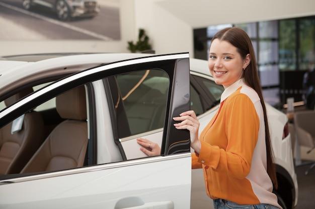 Великолепная счастливая молодая женщина покупает новую машину в автосалоне, копировальное пространство