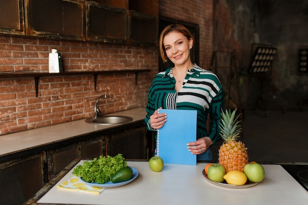 Gorgeous healthy young woman eating apple in her modern loft kitchen. fitness coach.