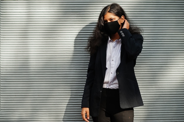 Великолепная индийская женщина носит формальную и черную маску для лица, позирует у стены во время пандемии covid.