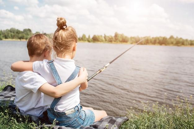 화려한 아이들이 호수 근처에 함께 앉아 서로 포옹하고 있습니다. 소녀는 낚시입니다. 그녀는 물고기 막대를 잡고있다. 그들은 혼자 있습니다.