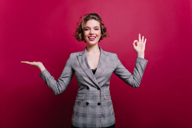 미소로 포즈를 취하는 공식적인 스타일의 옷에 화려한 아가씨. claret 벽에 고립 된 회색 재킷에 유행 여자의 실내 초상화.