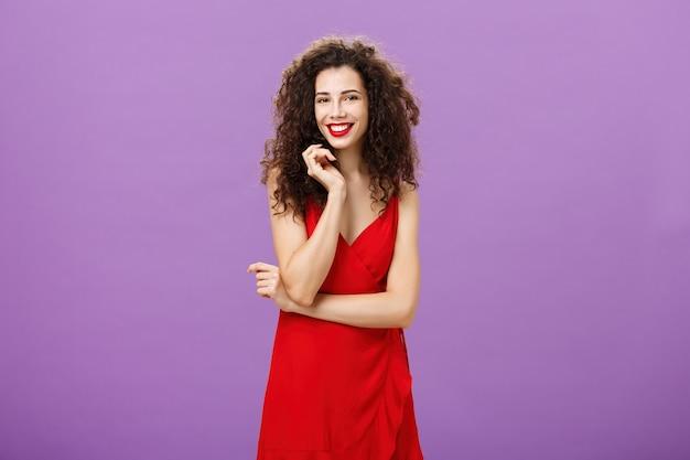 恥ずかしがり屋でぎこちない赤のゴージャスな女性が、紫の背景の上に臆病でフェミニンなダンスに招待され、広く笑っている巻き毛のストランドに触れ、胸に腕を組んでいます。