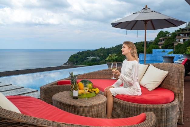 A gorgeous lady in white dress relaxing near pool. girl  sitting at rattan sofa and drinking white wine. enjoyng and relaxation