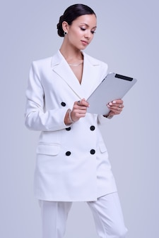 Gorgeous latin women in fashion white suit with digital tablet