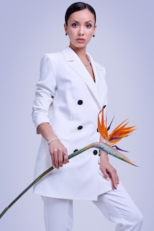 Gorgeous latin women in fashion white suit with exotic flower