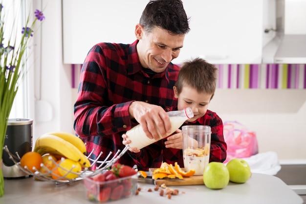 Великолепный маленький мальчик и его любящий отец лить молоко вместе в фруктовые смеси в миске блендера.