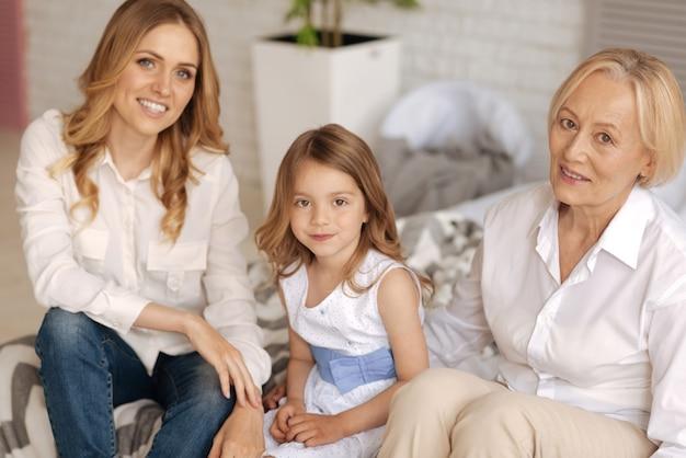 그녀의 매력적인 어머니와 할머니와 함께 자유 시간을 즐기는 귀여운 드레스에 화려한 어린 소녀가 모두 소파에 앉아 정면을 위해 포즈를 취합니다.