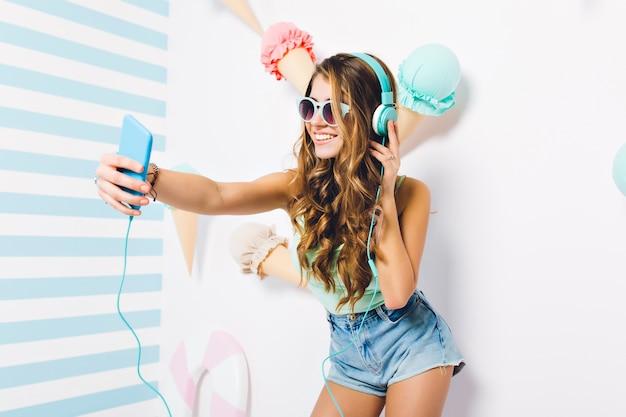 サングラスとデニムのショートパンツを身に着けているゴージャスな長い髪の少女が音楽を聴いている間に自分撮りを作ります。興奮した若い女性が装飾が施された壁に電話を保持している幸せそうな表情でポーズ。