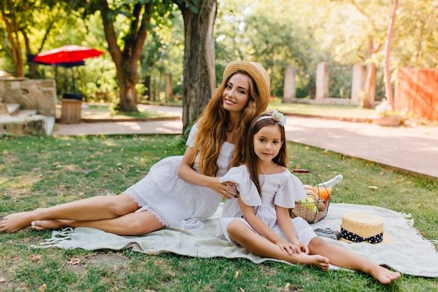 麦わら帽子と白いドレスを着たゴージャスな長髪の女性は、良い夏の日に娘とピクニックをします。公園で母親と一緒に時間を過ごすかわいい女の子の屋外の肖像画。