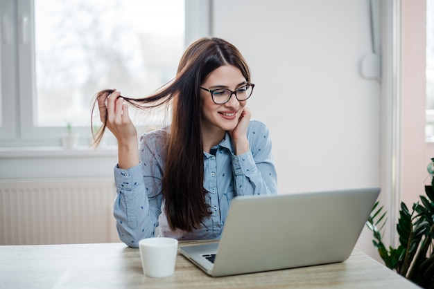 Gorgeous long haired woman looking at laptop computer, at home .