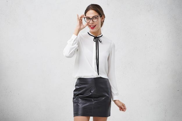 화려한 사랑스러운 여성 비서가 빨간 립스틱, 트렌디 한 안경, 블라우스 광고 스커트를 입는다.