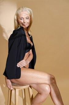下着とクラシックな黒のジャケットを着たゴージャスな成熟したブロンドの女性は、脇に笑みを浮かべて