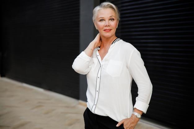 Великолепная деловая женщина средних лет с чашкой кофе, позирует на фоне черной стены.