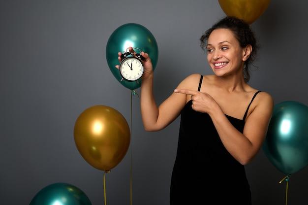 이브닝 드레스를 입은 멋진 혼혈 여성, 금색과 녹색 금속 공기 풍선으로 회색 배경 위에 격리된 알람 시계를 가리킵니다. 크리스마스, 새해, 생일 파티, 기념일