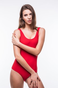 Gorgeous model girl in red swimming suite holds arms on her legs isolated on white background