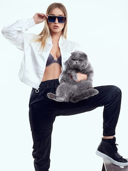 Gorgeous model girl in a tracksuit posing with a fat pedigree cat