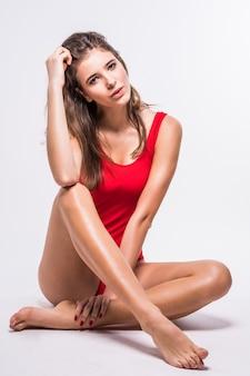 Великолепная модель с волосами брюнетки сидит на полу, одетая в красный купальный костюм на белом фоне