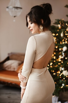 Gorgeous model woman with perfect body in evening dress with nude back posing in decorated interior