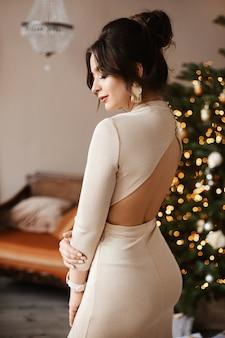 装飾されたインテリアでポーズをとって裸の背中とイブニングドレスで完璧なボディを持つゴージャスなモデルの女性