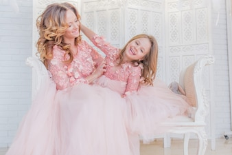 Gorgeous mom and daughter dressed like princesses in the same clothes pose