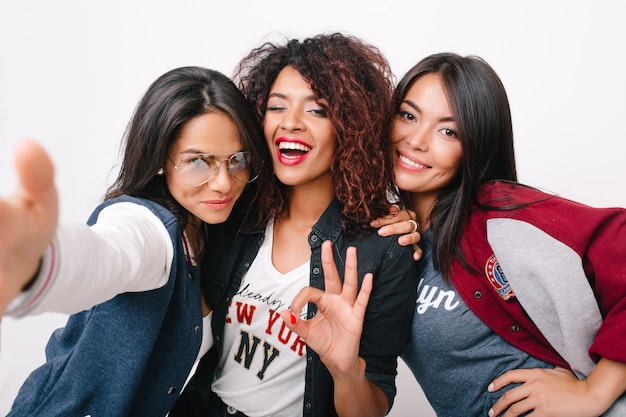 Gorgeous mulatto girl posing with ok sign between latin and asian friends. indoor portrait of pleased young women from different countries standing together with smiles.