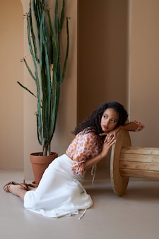 Gorgeous mulatto girl with curly hair posing near tall succulent plant in flower pot, sitting on floor and leaning on wooden wheel