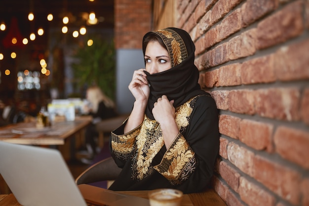 コーヒーショップに座っている間スカーフで顔を覆っている豪華なイスラム教徒の女性。机の上にはノートパソコンとコーヒーがあります。