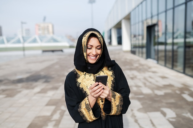 Gorgeous muslim woman dressed in black traditional wear standing on rooftop and using smart phone.